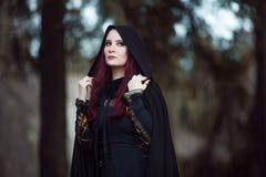 Jonge mooie en geheimzinnige vrouw in hout, in zwarte mantel met kap, beeld van boself of heks royalty-vrije stock foto