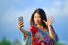Jonge mooie en gelukkige Aziatische Chinese toeristenvrouw op haar jaren '20 met kleurrijke kleding die selfie pic met mobiele te Royalty-vrije Stock Foto's