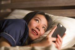 Jonge mooie en gelukkige Aziatische Japanse vrouw in pyjama's die mobiele telefoon sociale media gebruiken die met haar vriend of stock afbeeldingen