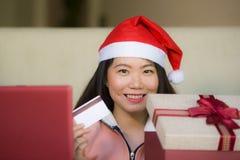 Jonge mooie en gelukkige Aziatische Koreaanse vrouw die de holdingscreditcard van de Kerstmanhoed en Kerstmis huidige doos dragen royalty-vrije stock foto's