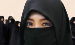 Jonge mooie en gelukkige Moslimvrouw die in de traditionele kleding van Islamburqa met verbazende expressieve ogen de camera beki royalty-vrije stock fotografie