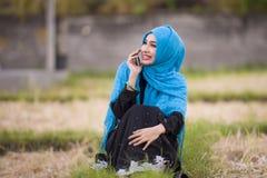 Jonge mooie en gelukkige moslimvrouw die Islamitische hijab hoofdsjaal en traditionele kleding dragen die op mobiele telefoon spr stock foto