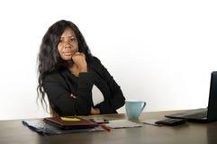 Jonge mooie en zekere zwarte afro Amerikaanse onderneemster die bij het bureau die van de bureaucomputer bazig en ontspant in vro stock afbeelding
