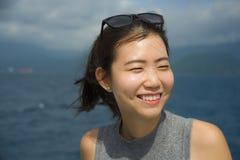 Jonge mooie en zoete Aziatische Chinese vrouw die gelukkig het genieten van zeebries glimlachen bij tropisch oceaanlandschap Stock Afbeeldingen