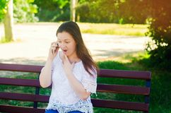 Jonge mooie Europese meisjes donkerbruine zitting op een bank in een stadspark en het spreken op de telefoon en verrast goed nieu royalty-vrije stock foto's