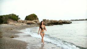 Jonge mooie gelooide vrouw die met lang haar in bikini op zandig strand bij zonsondergang lopen stock videobeelden