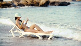 Jonge mooie gelooide vrouw met lang haar in bikini die op deckchair op strand liggen stock footage