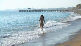 Jonge mooie gelooide vrouw met lang haar in bikini die op zandig strand lopen stock videobeelden