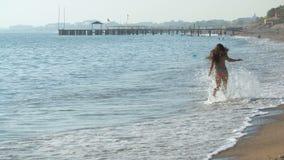 Jonge mooie gelooide vrouw met lang haar in bikini die op zandig strand lopen stock footage