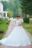 Jonge mooie gelukkige bruid met bloemboeket in park royalty-vrije stock afbeeldingen