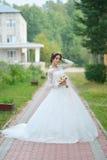 Jonge mooie gelukkige bruid met bloemboeket in park stock afbeeldingen