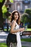 Jonge mooie gelukkige glimlachende dame die op de straat lopen, die document kop van koffie houden Model dragende modieuze kleren royalty-vrije stock fotografie