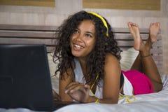 Jonge mooie gelukkige zwarte Afrikaanse Amerikaanse vrouwen thuis slaapkamer die vrolijk op bed die aan Internet-muziek met headp stock afbeeldingen