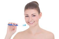 Jonge mooie glimlachende die vrouw met tandenborstel op wit wordt geïsoleerd Royalty-vrije Stock Afbeelding