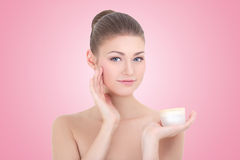 Jonge mooie glimlachende vrouw met roomfles over roze Stock Foto