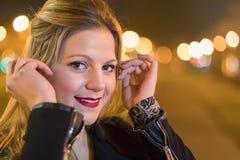 Jonge mooie glimlachende vrouw tegen nachtlichten Stock Afbeelding