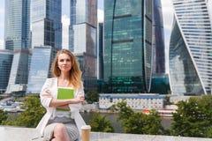 Jonge mooie het bureaugebouwen van de vrouwenzitting aganst Royalty-vrije Stock Foto's