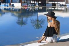 Jonge mooie het fluweelhuid van de meisjesglimlach, rode lippen, het zwarte zwempak stellen in de pool in blauw water, modieuze s Stock Foto
