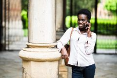Jonge mooie het meisjes sprekende telefoon van de afro Amerikaanse student op pauze openlucht in campus royalty-vrije stock foto's