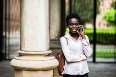 Jonge mooie het meisjes sprekende telefoon van de afro Amerikaanse student op pauze openlucht in campus stock foto's