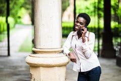 Jonge mooie het meisjes sprekende telefoon van de afro Amerikaanse student op pauze openlucht in campus royalty-vrije stock afbeelding
