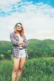 Jonge mooie hipstervrouw die gekruiste wapens in het midden van natur bevinden zich Stock Foto's
