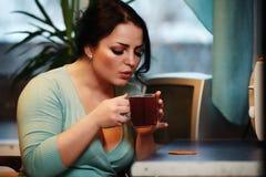 Jonge mooie huisvrouw het drinken thee in keuken stock foto