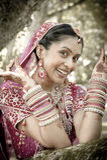 Jonge mooie Indische Hindoese bruid die onder boom met geschilderde opgeheven handen lachen Stock Fotografie