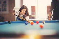 Jonge mooie jonge vrouw die het snookerschot pogen te nemen stock fotografie