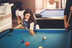 Jonge mooie jonge vrouw die het snookerschot pogen te nemen royalty-vrije stock fotografie