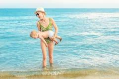 Jonge mooie kale moeder die het leuke Kaukasische duidelijke blauwe water van de peuterjongen uit dragen bij tropisch strand met  stock foto