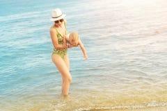 Jonge mooie kale moeder die het leuke Kaukasische duidelijke blauwe water van de peuterjongen uit dragen bij tropisch strand met  royalty-vrije stock foto