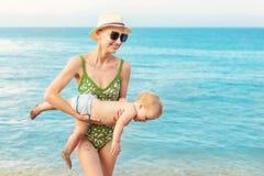 Jonge mooie kale moeder die het leuke Kaukasische duidelijke blauwe water van de peuterjongen uit dragen bij tropisch strand met  stock fotografie