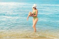 Jonge mooie kale moeder die het leuke Kaukasische duidelijke blauwe water van de peuterjongen uit dragen bij tropisch strand met  stock afbeeldingen