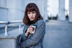 Jonge mooie Kaukasische bedrijfsvrouw op de straat met koffie na het werk dichtbij het moderne gebouw royalty-vrije stock afbeeldingen