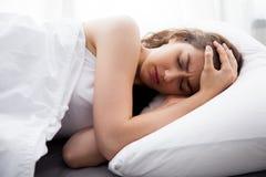 Jonge mooie Kaukasische vrouw op bed die hoofdpijn/slapeloosheid/migraine/spanning hebben Stock Afbeelding