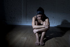 Jonge mooie Latijnse vrouw of tienermeisjeszitting droevig en alleen in het gespannen duisternis gedeprimeerd voelen Stock Afbeelding