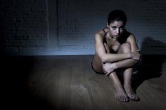 Jonge mooie Latijnse vrouw of tienermeisjeszitting droevig en alleen in het gespannen duisternis gedeprimeerd voelen Stock Foto's