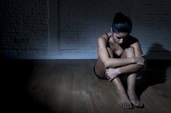 Jonge mooie Latijnse vrouw of tienermeisjeszitting droevig en alleen in het gespannen duisternis gedeprimeerd voelen Royalty-vrije Stock Foto