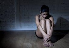 Jonge mooie Latijnse vrouw of tienermeisjeszitting droevig en alleen in het gespannen duisternis gedeprimeerd voelen Royalty-vrije Stock Afbeeldingen