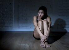 Jonge mooie Latijnse vrouw of tienermeisjeszitting droevig en alleen in het gespannen duisternis gedeprimeerd voelen Royalty-vrije Stock Fotografie