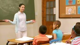 Jonge mooie leraar die les hebben aan kinderen stock video