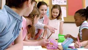 Jonge mooie leraar die les hebben aan kinderen stock videobeelden