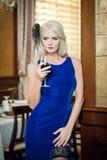Jonge mooie luxueuze vrouw in lange elegante kleding. Mooie jonge blondevrouw die in blauwe kleding een glas wijn houdt Royalty-vrije Stock Afbeelding