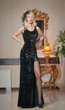 Jonge mooie luxueuze vrouw in lange elegante zwarte kleding Mooie jonge blondevrouw met grote gouden spiegel op achtergrond Stock Foto's