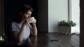 Jonge mooie meisje het drinken koffie in een koffie dichtbij een venster stock footage