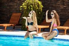 Jonge mooie meisjes die, begroeten, die dichtbij zwembad ontspannen glimlachen Royalty-vrije Stock Afbeeldingen
