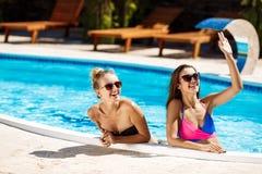 Jonge mooie meisjes die, begroeten, die in zwembad ontspannen glimlachen Stock Foto