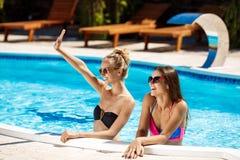 Jonge mooie meisjes die, begroeten, die in zwembad ontspannen glimlachen Royalty-vrije Stock Foto