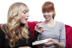 Jonge mooie meisjes die chocolade eten stock afbeelding